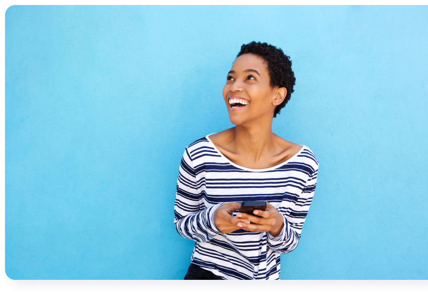 Black Woman Holding Phone Looking Up Smiling With Blue Background | Qube Money